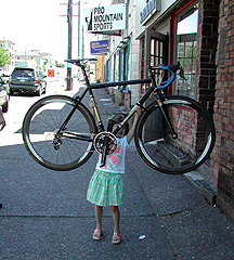 Grace Towle, 6, holds a bike above her head
